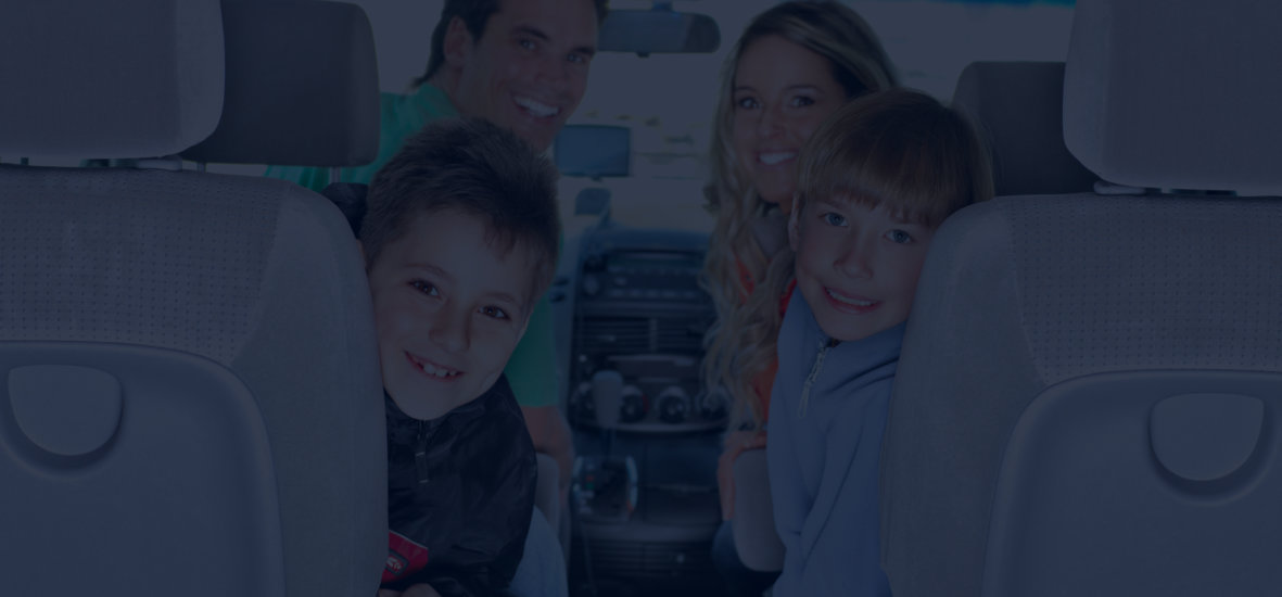 family smiling inside the car